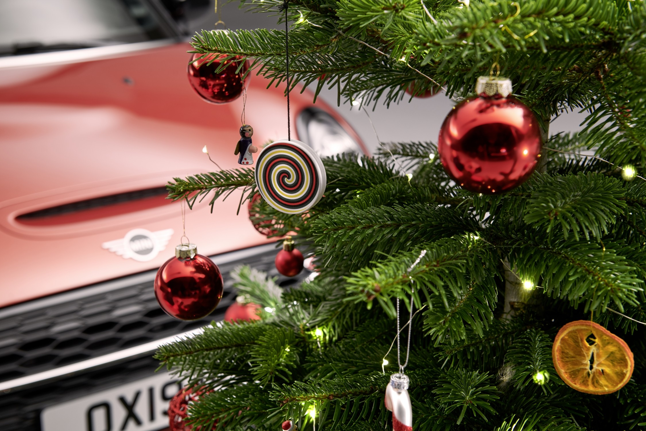 A mini cooper stand in back of a christmas tree